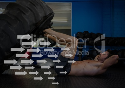 Fit man performing leg press exercise with tyre