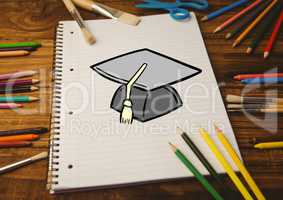 Drawn mortar board on notebook with color pencils on wooden table