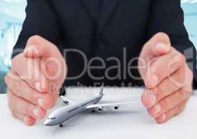 Airplane model surrounded by hands in gesture of protection