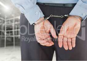 Corrupt businessman in handcuffs standing against built structure