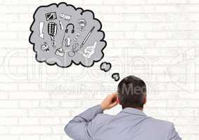 Rear view of businessman with thought bubble of various graphics