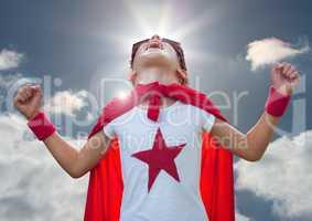 Kid in superhero costume screaming against sky in background