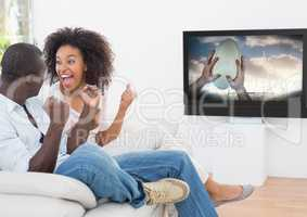 Excited couple watching rugby match on television in living room