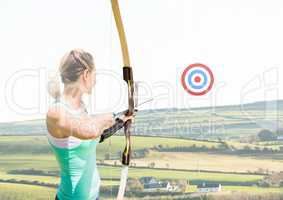 Athlete aiming at the target board against cityscape in background