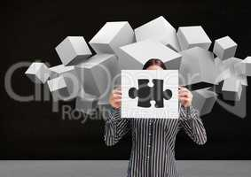 Businesswoman holding sheet of paper showing jigsaw puzzles and white cubes in backgrounds
