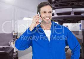 Mechanic talking on mobile phone at workshop