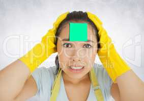 Worried female cleaner with sticky note on her forehead