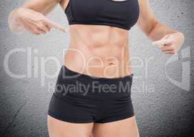 Mid section of fit woman pointing her abdomen