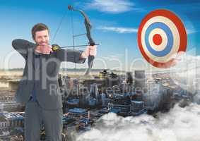Businessman aiming with bow and arrow at target over cityscape
