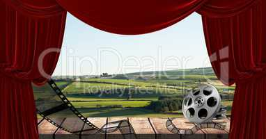 Film reel and curtain with scenic landscape in background