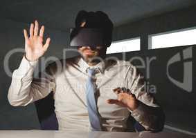 Businessman using virtual reality headset at desk