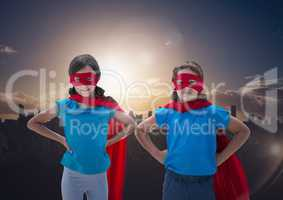 Smiling kids in red cape and mask standing with hand on hip against cityscape