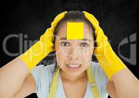 Cleaner with sticky note stuck o her face against black background