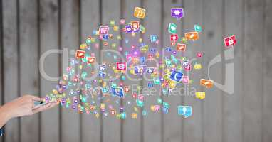 Man using smartphone with various application icons against wooden background