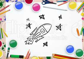 Rocket and stars drawn on paper surrounded with various watercolor and pencils