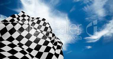 Checkered flag waving against cloudy sky