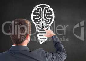 Rear view of businessman touching innovative bulb on grey background
