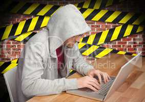 Man working on laptop at desk against caution taped wall in background