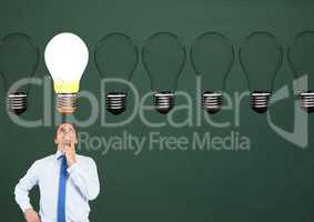 Businessman looking at glowing bulb against green background