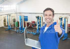 Mechanic with laptop showing thumbs up against garage in background