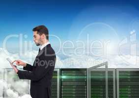 Digital composite image of businessman using digital tablet against server tower
