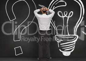 Stressed man standing against question mark and bulb drawn on wooden background