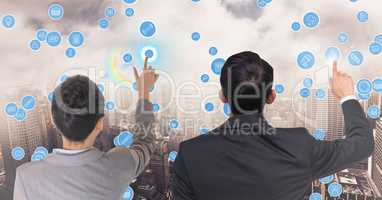 Business executives touching technology icons against cityscape