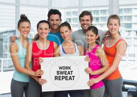 Group of people holding card with text  work, sweat and repeat in front of window in gym