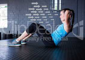 Fit woman performing crunches exercise in gym against direction arrows in background