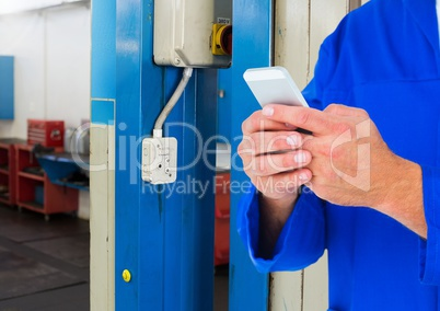 Automobile mechanic using mobile phone in workshop