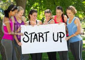 Fit healthy women holding placard that reads start up