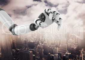 Robot hand over cityscape against cloudy sky