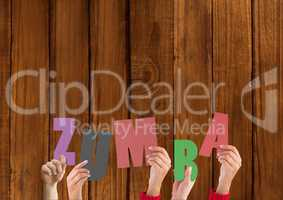 Hands holding word Zumba against wooden background