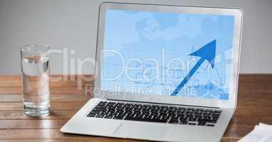 Laptop and glass of water on wooden table