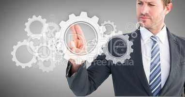 Businessman touching cog wheel on digital screen against grey background