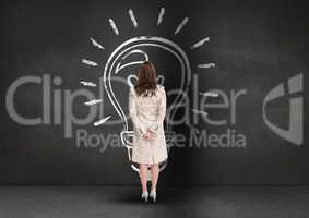 Rear view of businesswoman looking at innovative bulb on grey background