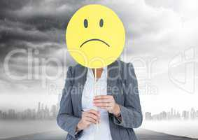 Businesswoman holding a smiley face in front of her face with rain clouds in background