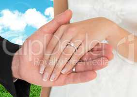Married couple holding hands against sky in background