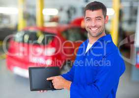 Happy automobile mechanic holding a digital tablet