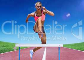 Female athlete jumping over hurdle on race track