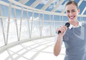 Composite image of a businesswoman holding a mic