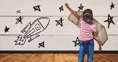 Kid pretending to be a pilot against stars and rocket drawn on background