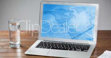Laptop with business chart screen and glass of water