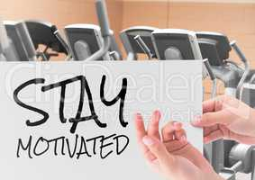 Female hand holding placard with text stay motivated in gym