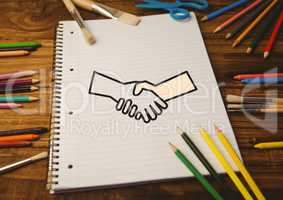 Drawn handshake shape on notebook with color pencils on wooden table