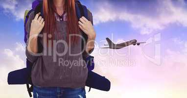 Tourist woman with backpack against airplane in sky