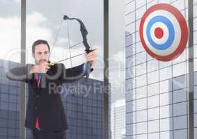 Businessman aiming at the target board against office buildings in background