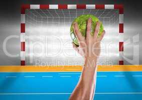 Athlete throwing handball against stadium in background
