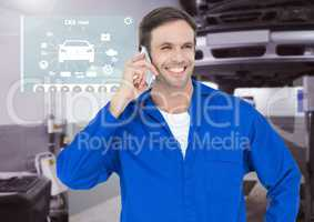 Happy automobile mechanic talking on mobile phone