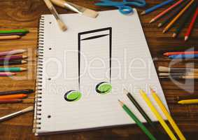 Spiral notepad with music sign and colored pencils on table